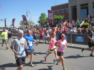 Finishing my first half marathon, smiling behind the guy in the blue